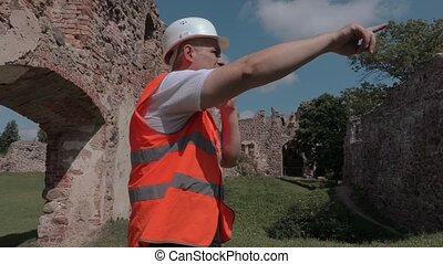 Builder talking and shows gestures in the castle yard