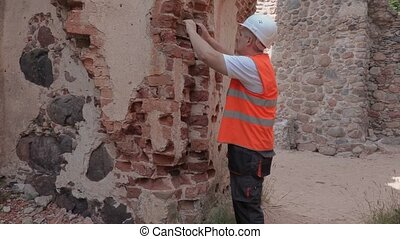 Builder checking the old castle's wall before restoration