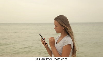 Girl with a tablet in hand on the beach