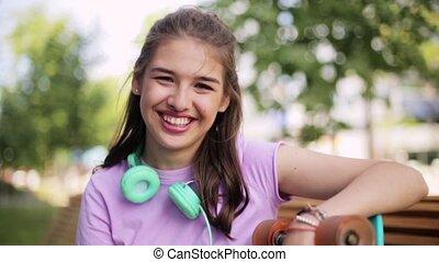 happy teenage girl with headphones and longboard -...