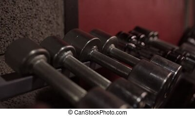 man taking dumbbells from storage rack in gym - fitness,...