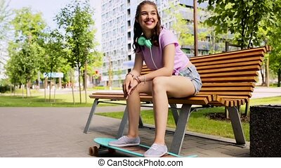 happy teenage girl with headphones and longboard -...