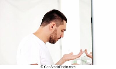 man applying after shave oil to face at bathroom - beauty,...