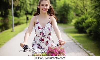 happy young woman riding bicycle in summer park - people,...