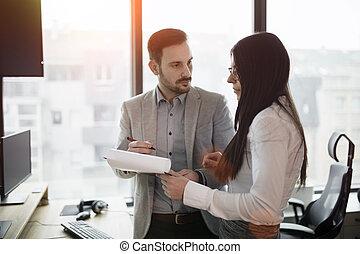 Picture of business couple discussing in office