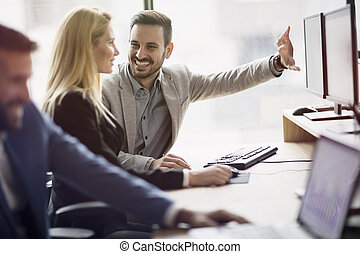 Portrait of cheerful business couple working on computer in...