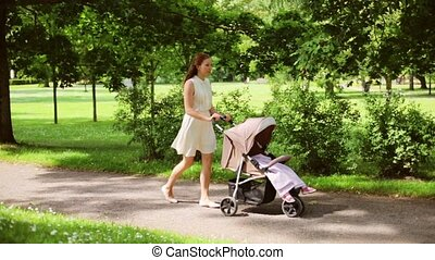 happy mother with baby in stroller walking at park - family,...