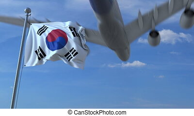 Commercial airplane landing behind waving Korean flag....