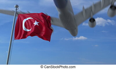 Commercial airplane landing behind waving Turkish flag....