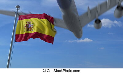 Commercial airplane landing behind waving Spanish flag....