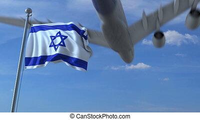 Commercial airplane landing behind waving Israeli flag....
