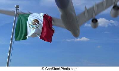Commercial airplane landing behind waving Mexican flag....