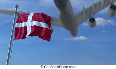 Commercial airplane landing behind waving Danish flag....