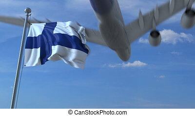 Commercial airplane landing behind waving Finnish flag....