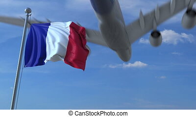Commercial airplane landing behind waving French flag....