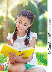 Portrait of pretty young girl reading book in park -...