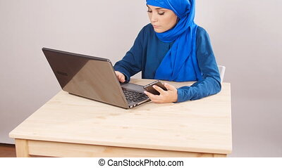 Young Muslim woman sitting in office and working on laptop