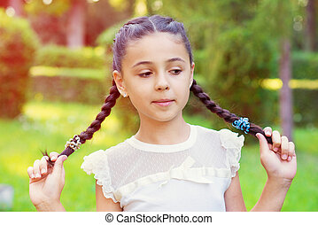 Portrait of pretty young girl with pigtails at sunny day in...