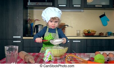 Cute little girl sifting flour for cake on kitchen table....