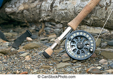 Close up of fly fishing rod and reel on riverbank