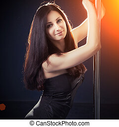 beautiful young woman posing next to pole