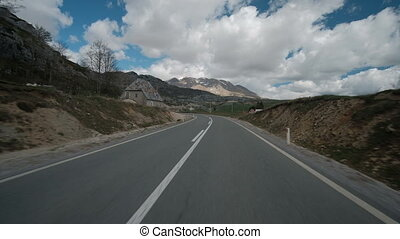 Traffic on the flat road to the mountains in the spring. On...