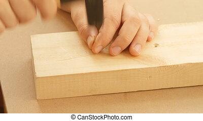 Man hitting nail by hammer - Close up of man hitting nail by...