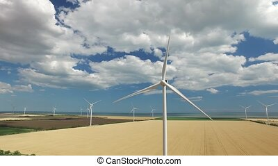 Wind farms on the background of yellow and green fields near...