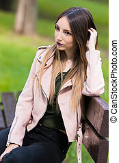 Portrait of informal fashionable girl on bench in park -...