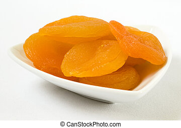 Dried apricots in a vas on a white background