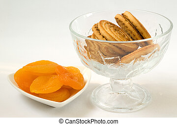 Dried apricots and cookies in a vas on a white background