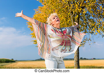 Active senior woman feeling free and happy while standing...