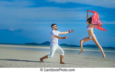 An elegant couple having fun at a desert beach
