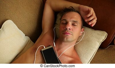 Person sleeping in the day on the couch with headphones from...