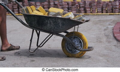 Construction Worker is Driving a Wheelbarrow with Paving...