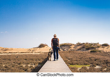 Man with dog walking on the wooden path on the beach and...