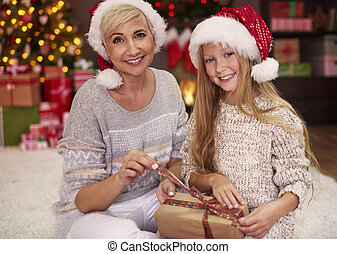 Mother and daughter unwrapping some Christmas gifts