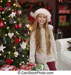 Charming girl next to the Chistmas tree
