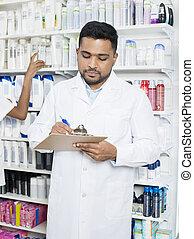 Male Pharmacist Holding Clipboard Against Shelves