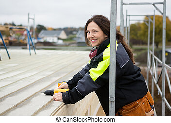 Female Carpenter Smiling While Holding Drill Machine At Roof...