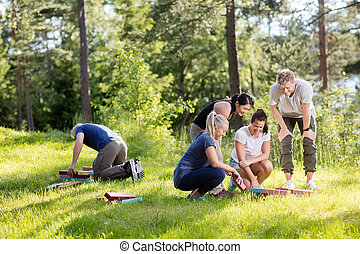 Friends Arranging Building Blocks On Grassy Field -...