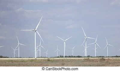 Blades of wind turbines rotate from the wind tree leaves and...