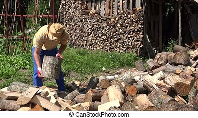 farmer man split log with axe village yard near wood pile....