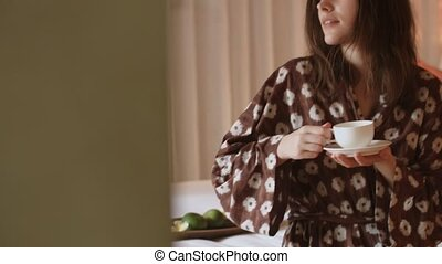 Beautiful woman drinking coffee and relaxing in the bedroom...