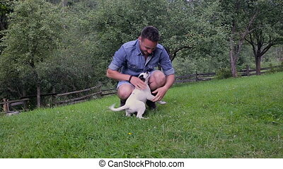 Young handsome man playing with puppy in the garden