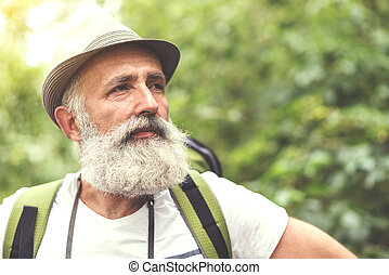 Thoughtful senior male tourist relaxing in woodland -...