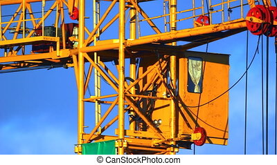 Extreme close-up of working tower crane cabin at sunset -...
