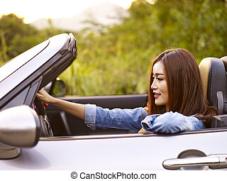 young asian woman riding in a convertible car - young asian...