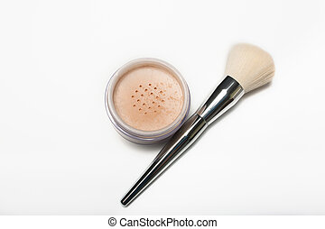 Mineral loose powder and cosmetic brush on a white background