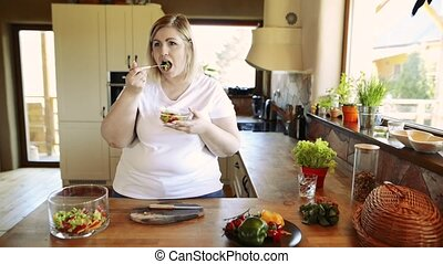 Overweight woman at home eating vegetable salad in the...